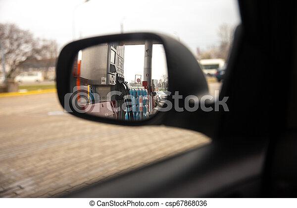 Una ventana trasera en un retrovisor durante una parada en una gasolinera - csp67868036