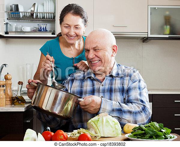Una pareja sonriente cocinando juntos - csp18393802