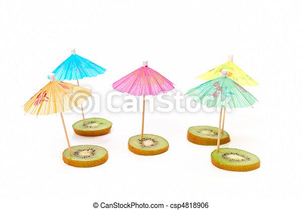 cocktail umbrellas on the slices of kiwi - csp4818906
