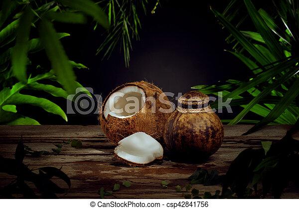 Cierren la vista de un bonito coco fresco en el fondo de hojas verdes - csp42841756