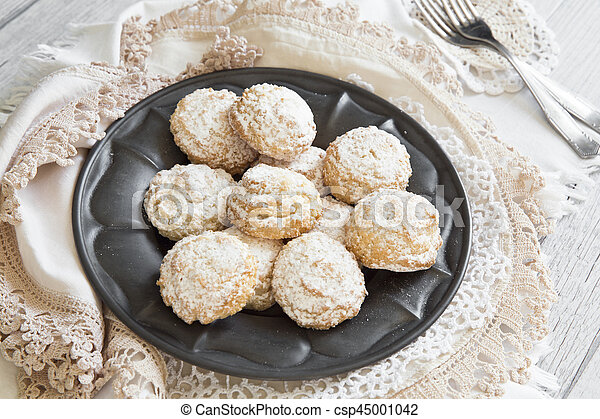 Coconut biscuits with icing sugar over pewter plate - csp45001042