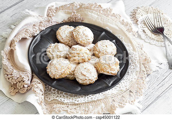 Coconut biscuits with icing sugar over pewter plate - csp45001122