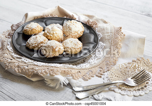 Coconut biscuits with icing sugar over pewter plate - csp45001004