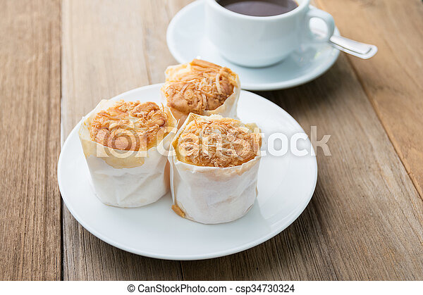 coconut cupcake with coffee on wood table - csp34730324