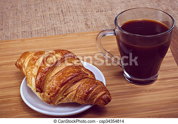 Coffee and croissant for breakfast on rustic wooden table - csp34354814