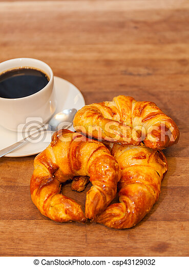 Coffee and croissant for breakfast on rustic wooden table, top view - csp43129032