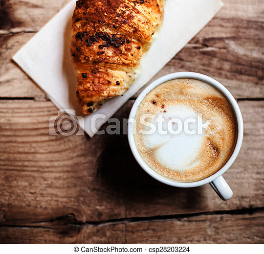 Coffee and fresh croissant for breakfast on rustic wooden table, top view. Chocolate croissant - csp28203224