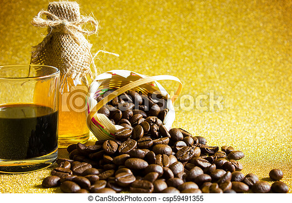 Coffee beans and Black coffee cup and Honey in the bottleon on golden background. - csp59491355