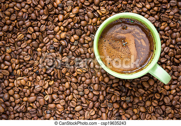 Coffee beans and green cup - csp19635243