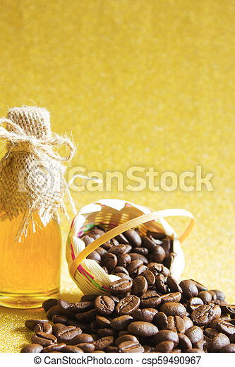 Coffee beans and Honey in the bottleon on golden background. - csp59490967