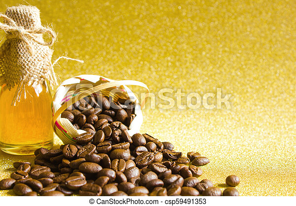 Coffee beans and Honey in the bottleon on golden background. - csp59491353