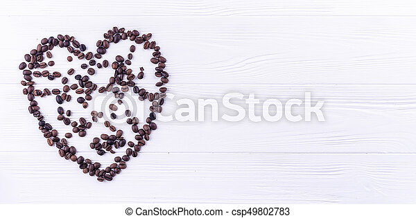 Coffee beans in a form of a heart on a white wooden background with a space for your text - csp49802783