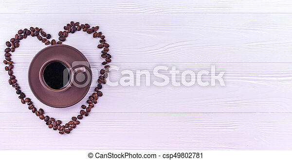 Coffee beans in a form of a heart with a cup of coffee on a white wooden background - csp49802781