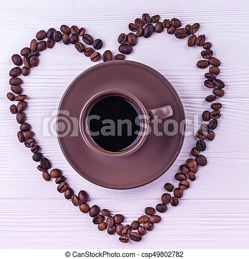 Coffee beans in a form of a heart with a cup of coffee on a white wooden background - csp49802782