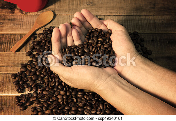 Coffee beans in the hand of a woman show love - csp49340161