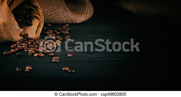 Coffee beans on a dark wooden background with space for your text - csp49802800