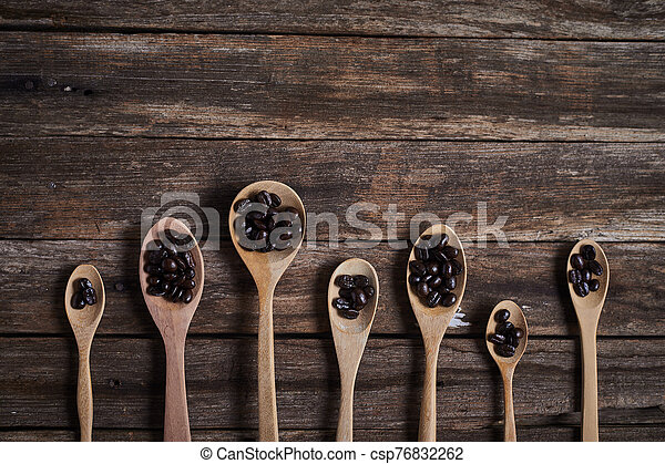 Coffee beans on wooden spoon. - csp76832262