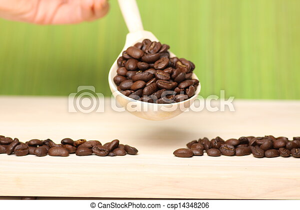 coffee beans on wooden table with spoon - csp14348206