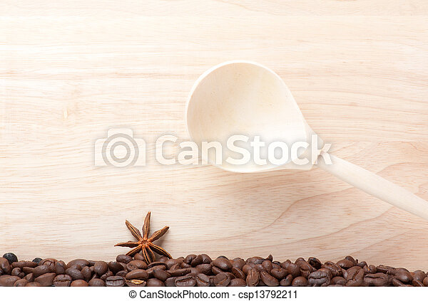 coffee beans on wooden table with wooden spoon - csp13792211