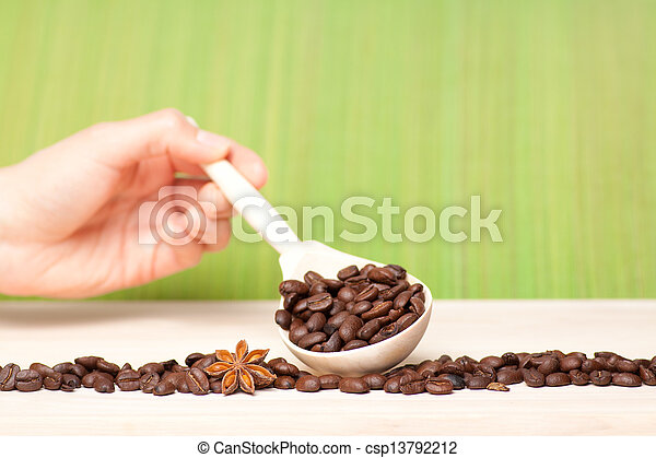 coffee beans on wooden table with wooden spoon - csp13792212