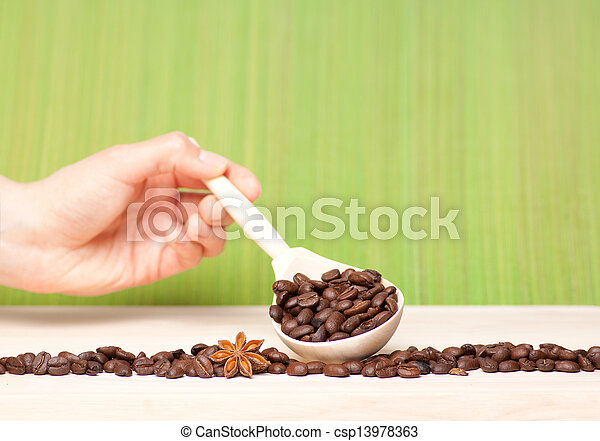 coffee beans on wooden table with wooden spoon - csp13978363