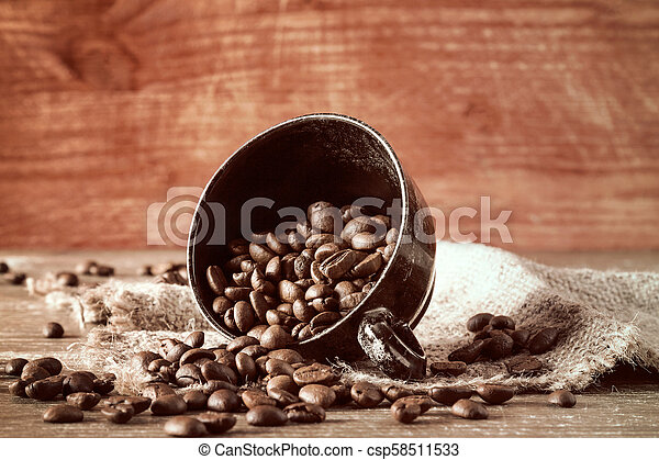 Coffee beans spilled out of a cup - csp58511533