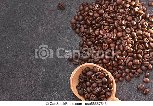 Coffee beans with wooden spoon on the table - csp66557543