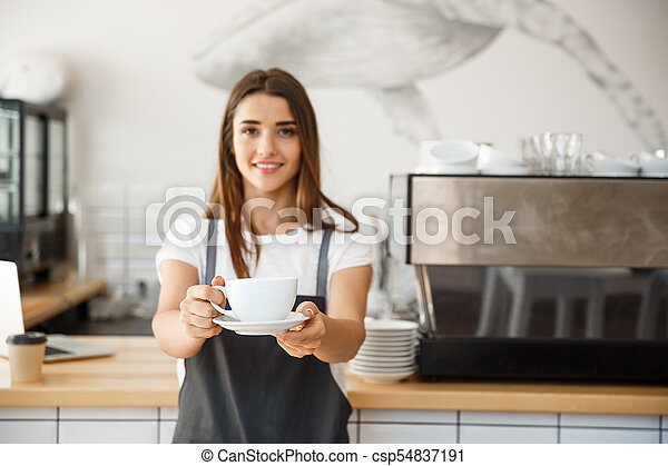 Coffee Business Concept - Caucasian female serving coffee while standing in coffee shop. Focus on female hands placing a cup of coffee. - csp54837191