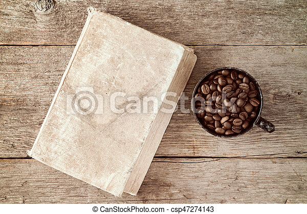 Coffee cup and coffee beans with old book - csp47274143