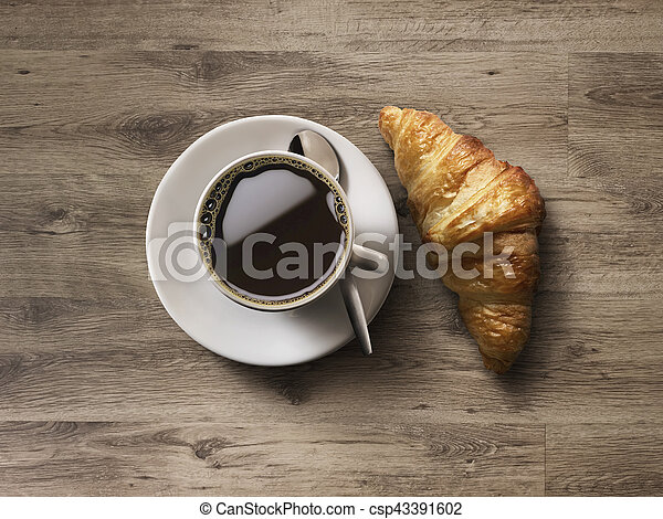 Coffee cup and fresh baked croissants on wooden background. - csp43391602