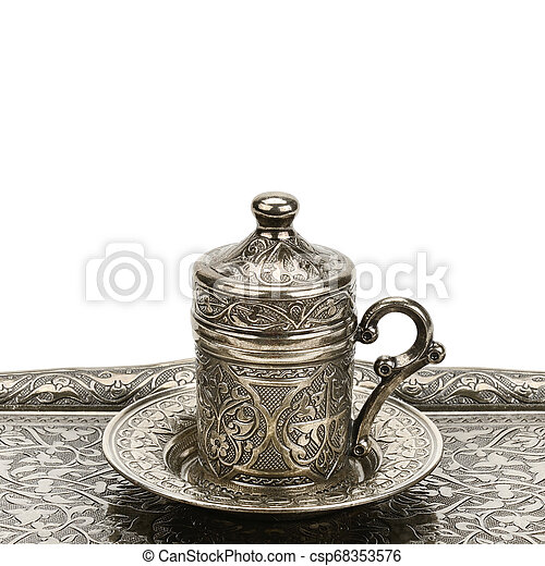 Coffee cup and tray with arabic decoration with metal cup and dish isolated on a white background. Free space for text. - csp68353576