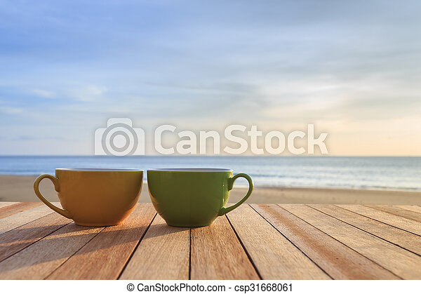 Coffee Cup On Wood Table At Sunset Or Sunrise Beach Close Up Coffee Cup On Wood Table At Sunset Or Sunrise Beach Canstock