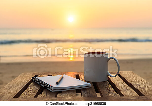 Coffee cup on wood table at sunset or sunrise beach - csp31668836