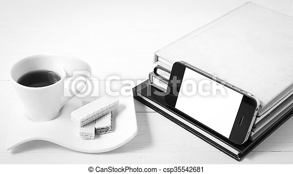 coffee cup with wafer, phone, stack of book black and white color - csp35542681