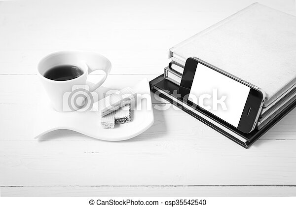 coffee cup with wafer, phone, stack of book black and white color - csp35542540
