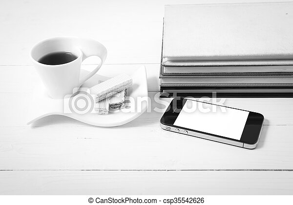 coffee cup with wafer, phone, stack of book black and white color - csp35542626