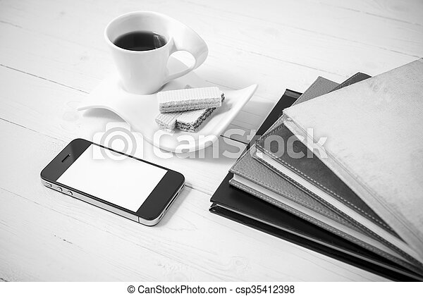 coffee cup with wafer, phone, stack of book black and white color - csp35412398