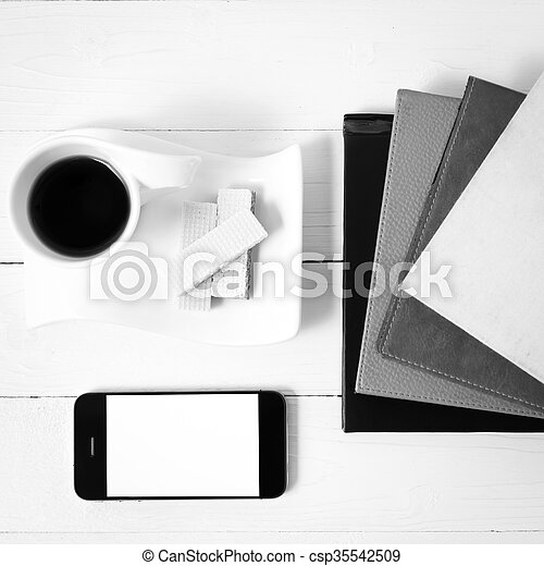 coffee cup with wafer, phone, stack of book black and white color - csp35542509