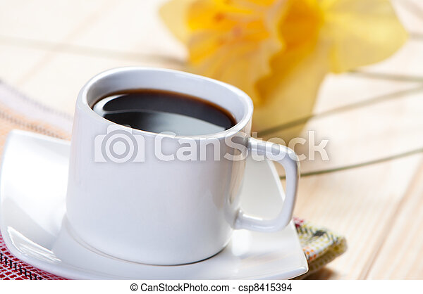 Coffee in white cup on background of yellow flower. - csp8415394