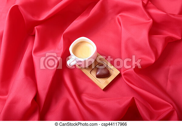 Coffee in white cup with chocolate pralines on red background - csp44117966