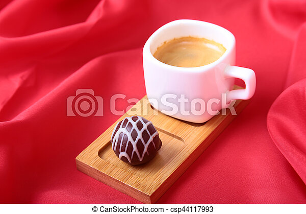 Coffee in white cup with chocolate pralines on red background - csp44117993