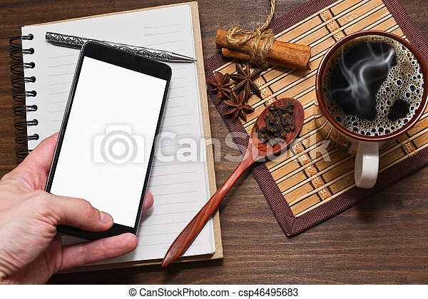 Coffee with spices, diary and a cell phone in hand - csp46495683