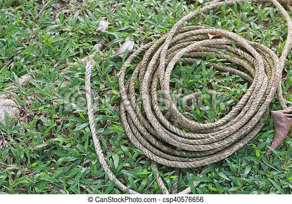 Coiled roll of rope arranged on grass ground with sunlight - csp40576656