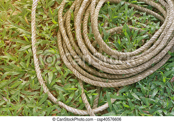 Coiled roll of rope arranged on grass ground with sunlight - csp40576606