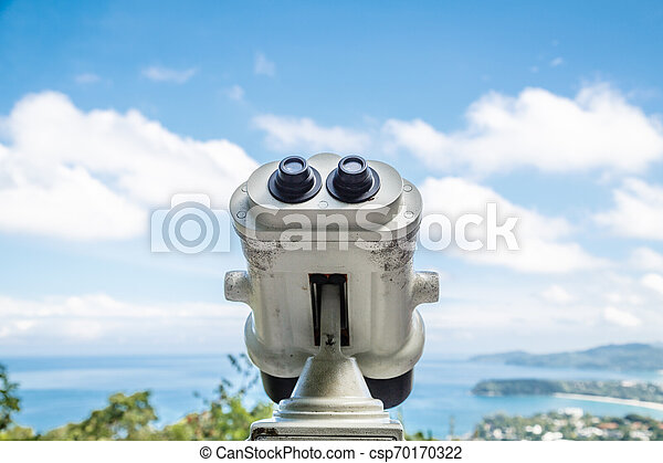 Coin Operated Binocular viewer next to the waterside promenade in Phuket looking out to the Bay. Landscape with beautiful cloudy sky and sea - csp70170322