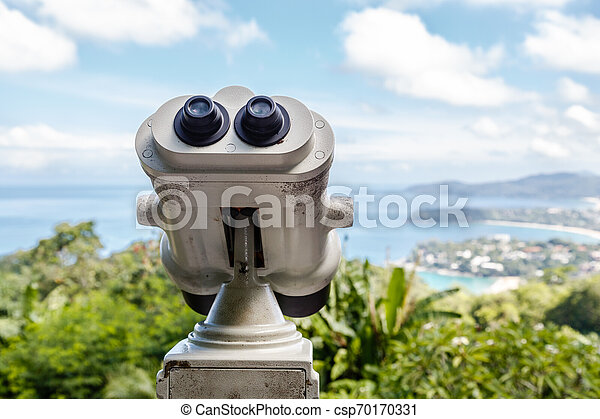 Coin Operated Binocular viewer next to the waterside promenade in Phuket looking out to the Bay. Landscape with beautiful cloudy sky and sea - csp70170331