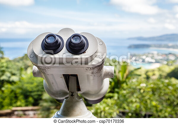 Coin Operated Binocular viewer next to the waterside promenade in Phuket looking out to the Bay. Landscape with beautiful cloudy sky and sea - csp70170336