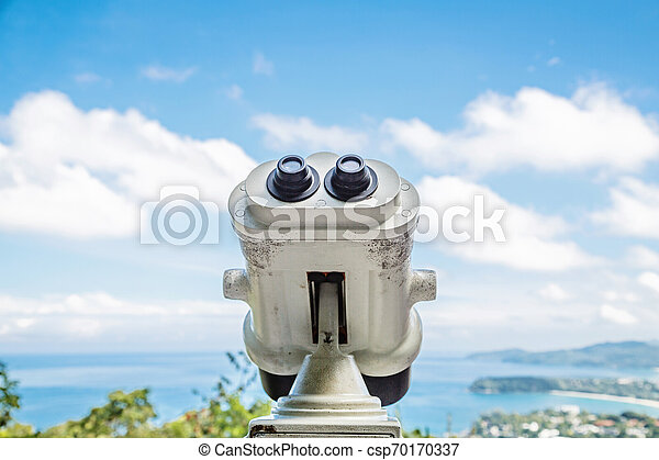 Coin Operated Binocular viewer next to the waterside promenade in Phuket looking out to the Bay. Landscape with beautiful cloudy sky and sea - csp70170337