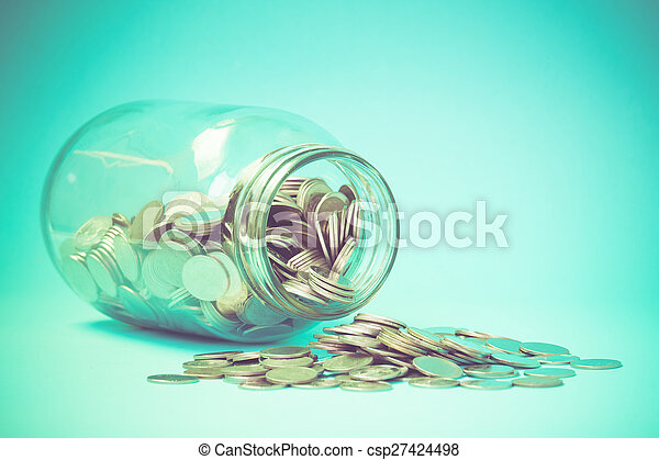 Coins spilling out of a glass bottle with filter effect retro vintage style - csp27424498