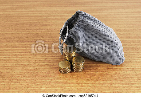 coins stack and money bag on wooden table background - csp53195944